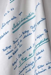 Emanuel Mathias, Abmahnung 1, BB 1969, 2013, Stickerei auf Baumwolle, mehrfarbig, 100 x 150 cm, mit Wäschestärke gestärkt, auf Haken drapiert